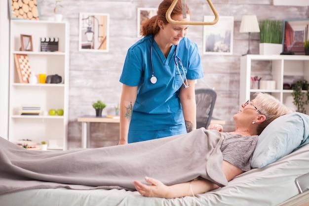 Ärztin im pflegeheim im gespräch mit einer älteren frau, die vor dem einschlafen im bett liegt.