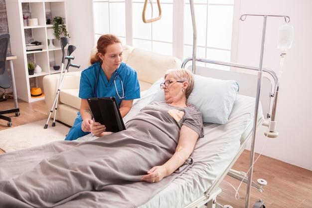 Ärztin im pflegeheim sitzt neben einer älteren frau, die mit ihrem tablet-computer im bett liegt.