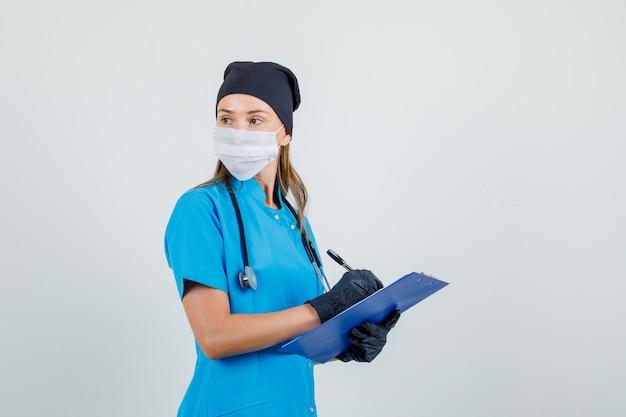 Ärztin im rückblick beim schreiben auf zwischenablage in uniform, handschuhen, maske und ernstem aussehen.