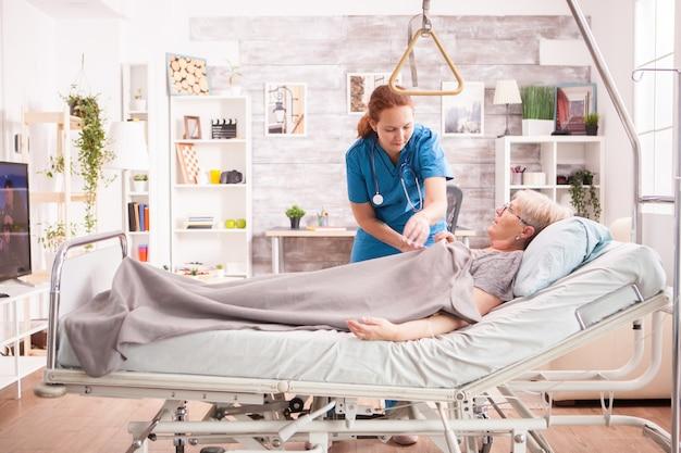 Ärztin im ursing-haus kümmert sich um die alte frau, die im bett liegt.