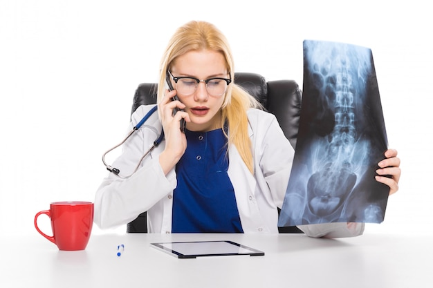 Ärztin im weißen mantel studiert sorgfältig röntgenstrahl