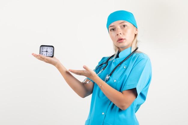 Ärztin in blauer uniform, die auf uhr zeigt und vorsichtig schaut
