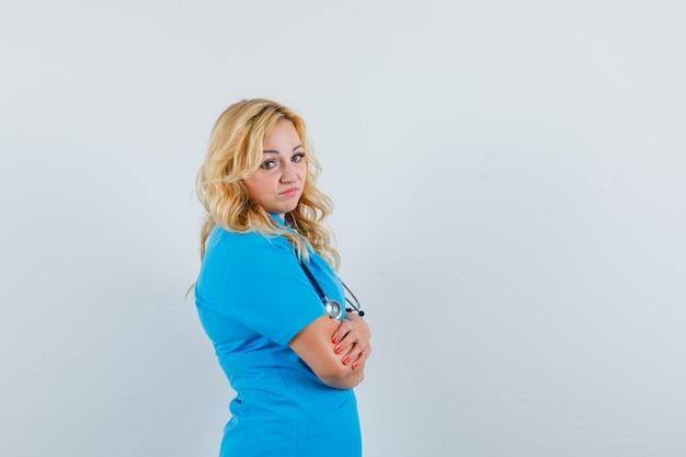 Ärztin in blauer uniform, die beiseite schaut und verärgert schaut. platz für text