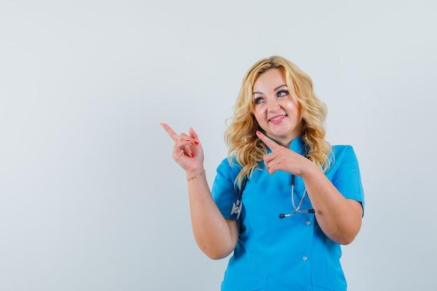 Ärztin in blauer uniform, die beiseite zeigt und optimistischen raum für text sucht