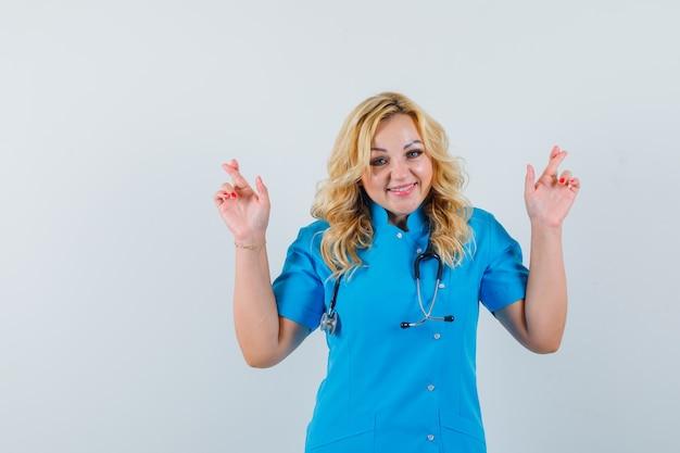 Ärztin in blauer uniform, die daumen drückt und fröhlich aussieht