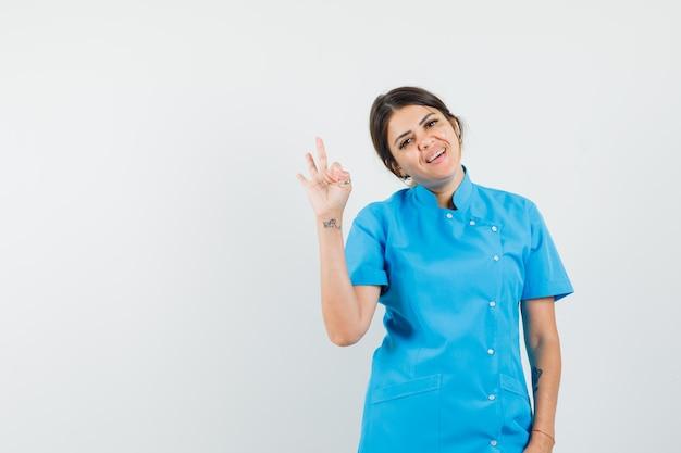 Ärztin in blauer uniform, die eine ok geste zeigt und fröhlich aussieht