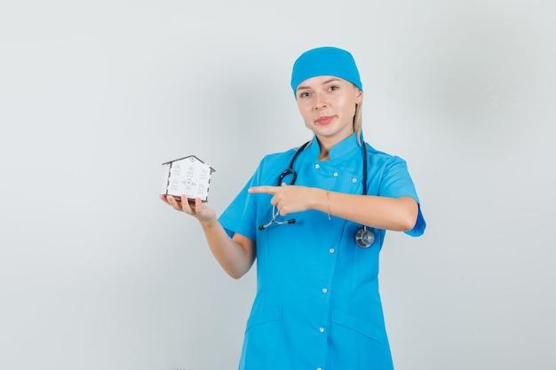 Ärztin in blauer uniform, die finger auf hausmodell zeigt und fröhlich schaut