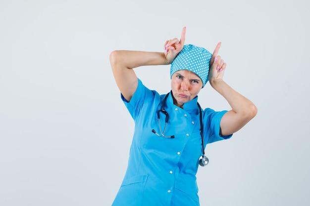 Ärztin in blauer uniform, die finger über kopf als stierhörner hält und lustige vorderansicht schaut.