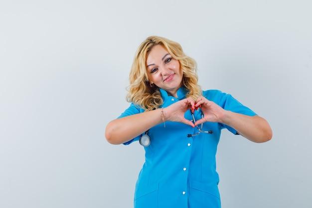 Ärztin in blauer uniform, die friedensgeste zeigt und geliebt aussieht,