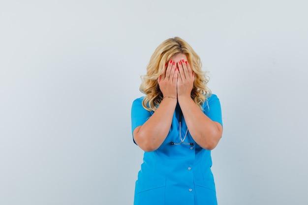 Ärztin in blauer uniform, die gesicht mit händen bedeckt und verärgerten raum für text sucht