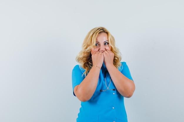 Ärztin in blauer uniform, die hände auf mund hält und ängstlich schaut