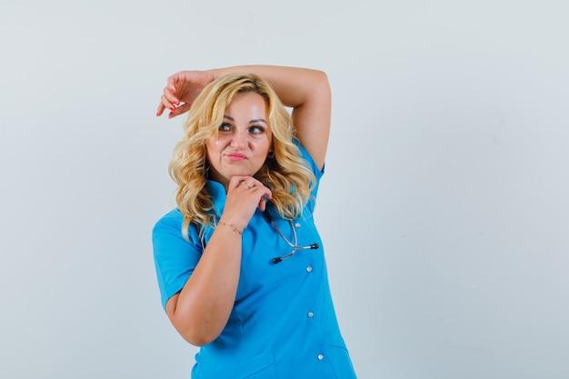 Ärztin in blauer uniform, die hand auf kopf hält, während sie posiert und selbstbewusst aussieht