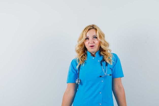 Ärztin in blauer uniform, die raum für text wegschaut