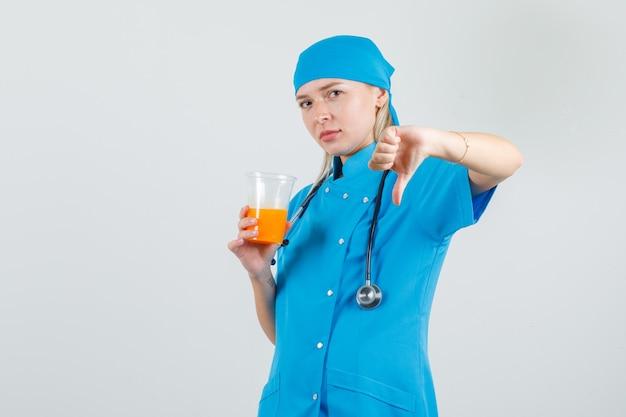 Ärztin in blauer uniform, die saftglas mit daumen nach unten hält und verärgert schaut