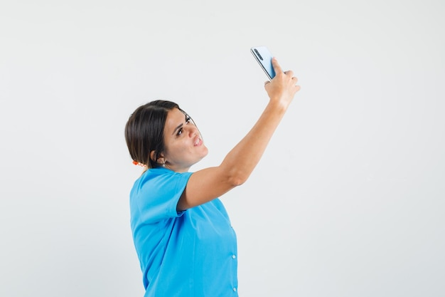 Ärztin in blauer uniform, die selfie auf dem handy macht und fröhlich aussieht looking