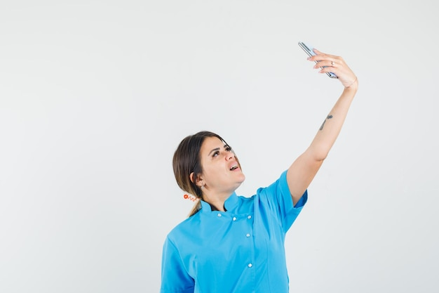 Ärztin in blauer uniform, die selfie auf dem handy macht und fröhlich aussieht