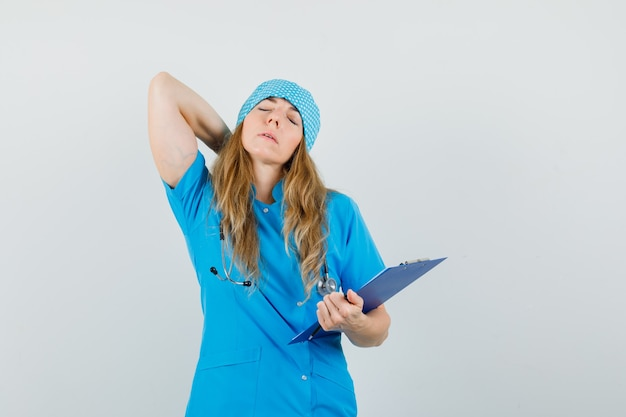 Ärztin in blauer uniform, die unter nackenschmerzen leidet, während sie zwischenablage hält und müde aussieht