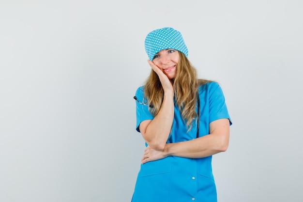 Ärztin in blauer uniform, die wange auf erhobene handfläche lehnt und verträumt aussieht