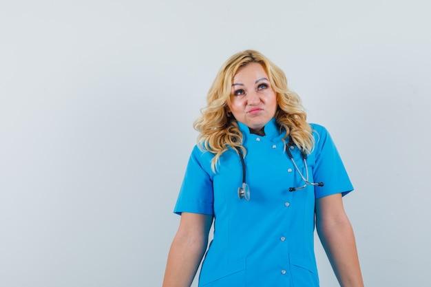 Ärztin in blauer uniform, die wegschaut und hilflos schaut, raum für text
