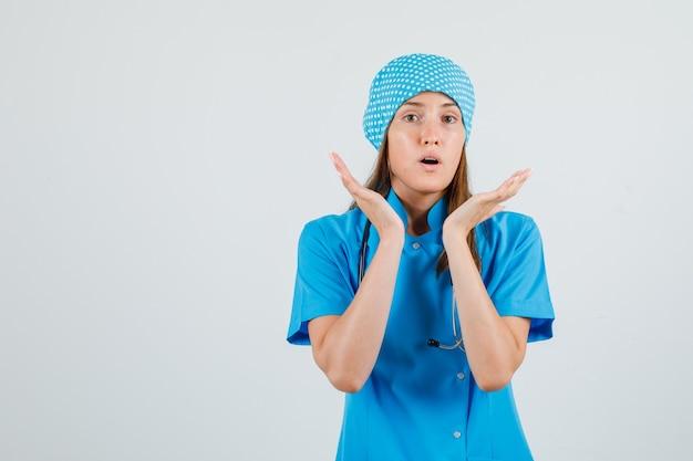 Ärztin in blauer uniform hält erhobene handflächen und sieht überrascht aus