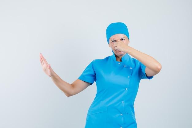 Ärztin in blauer uniform kneift die nase wegen schlechten geruchs und sieht angewidert aus, vorderansicht.