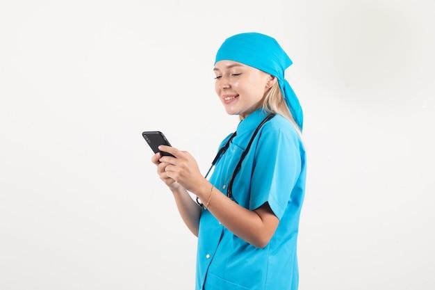 Ärztin in blauer uniform lächelnd beim tippen auf smartphone