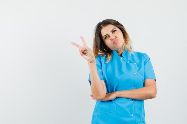 Ärztin in blauer uniform mit victory-zeichen, schmollende lippen