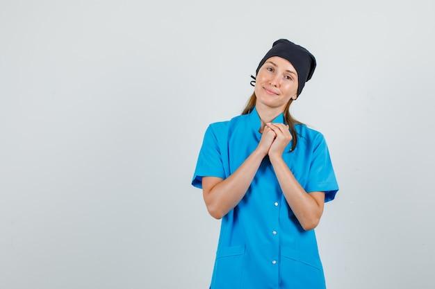Ärztin in blauer uniform, schwarzer hut, der die hände faltet und hoffnungsvoll aussieht