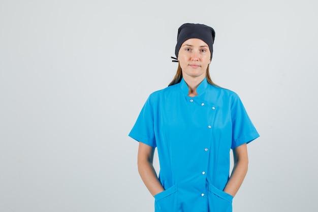 Ärztin in blauer uniform, schwarzer hut hält hände in taschen und sieht still aus