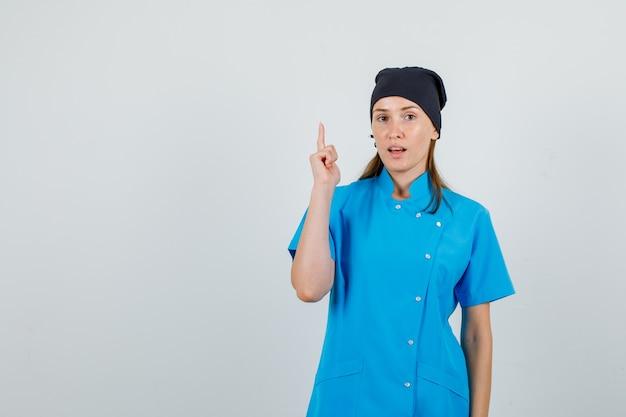 Ärztin in blauer uniform, schwarzer hut zeigt mit dem finger nach oben und sieht selbstbewusst aus