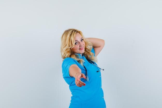 Ärztin in blauer uniform zeigt auf die kamera, während sie posiert und schön aussieht,