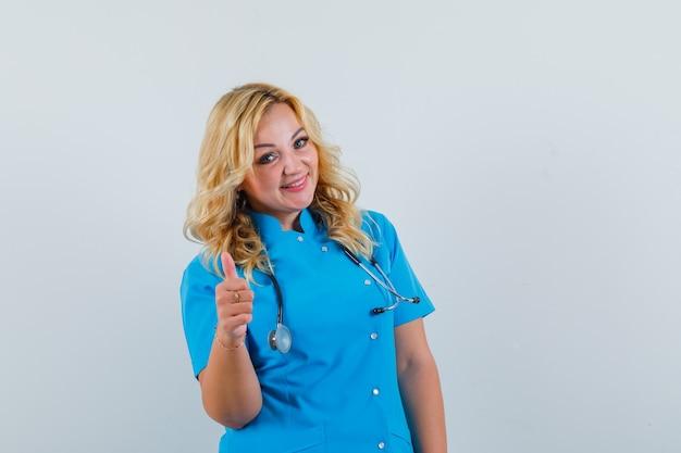 Ärztin in blauer uniform zeigt daumen hoch und sieht glücklich aus