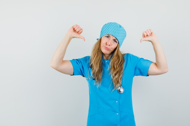 Ärztin in blauer uniform zeigt mit dem daumen auf sich