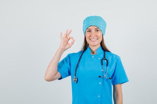 Ärztin in blauer uniform zeigt ok geste und sieht fröhlich aus