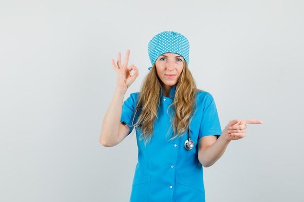 Ärztin in blauer uniform zeigt ok-zeichen, während sie zur seite zeigt und fröhlich aussieht