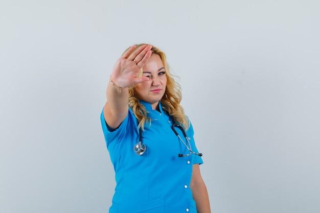 Ärztin in blauer uniform zeigt stoppgeste und sieht ernst aus