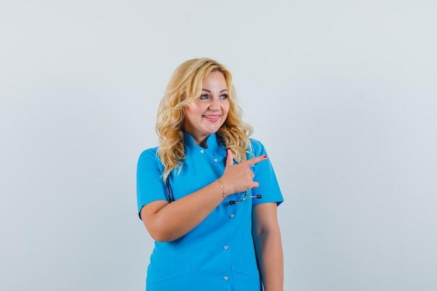 Ärztin in blauer uniform zeigt zur seite und sieht optimistisch aus