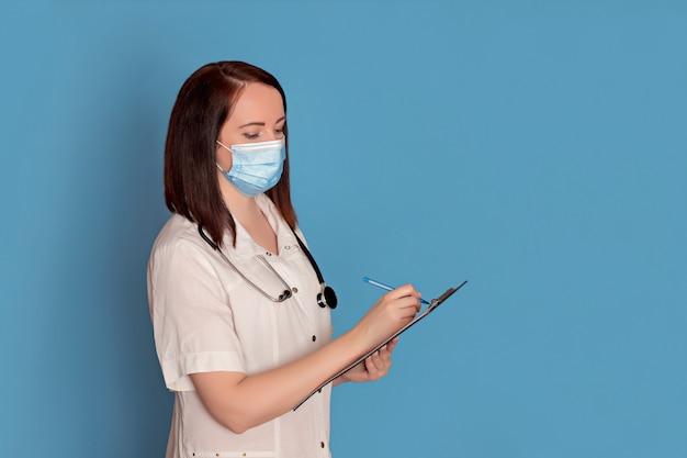 Ärztin in der medizinischen maske mit einem stethoskop schreibt auf einer tablette auf einem blauen hintergrund, kopienraum