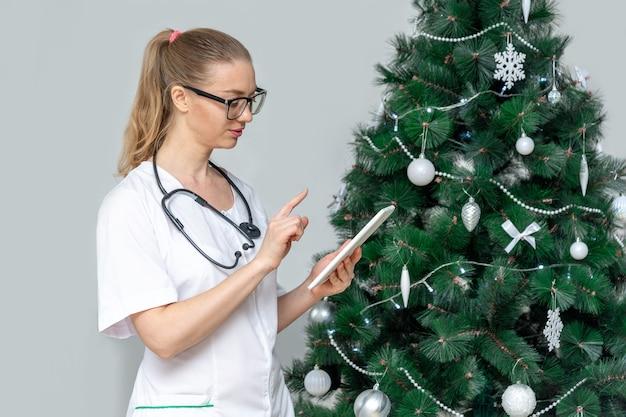 Ärztin in einer medizinischen schutzmaske hält eine tablette im hintergrund eines weihnachtsbaumes
