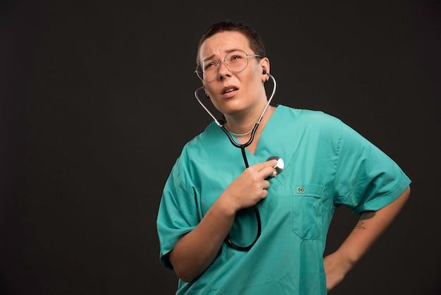 Ärztin in grüner uniform hält ein stethoskop und hört auf ihren herzschlag.