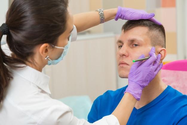 Ärztin in handschuhen bereitet das gesicht des patienten auf die operation vor