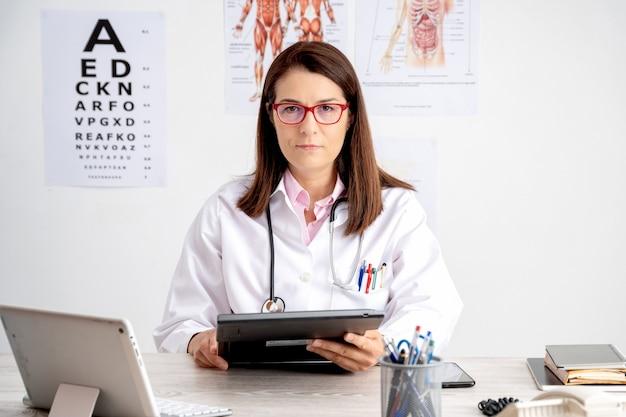 Ärztin in ihrem büro, die kamera mit tablette in ihren händen betrachtet