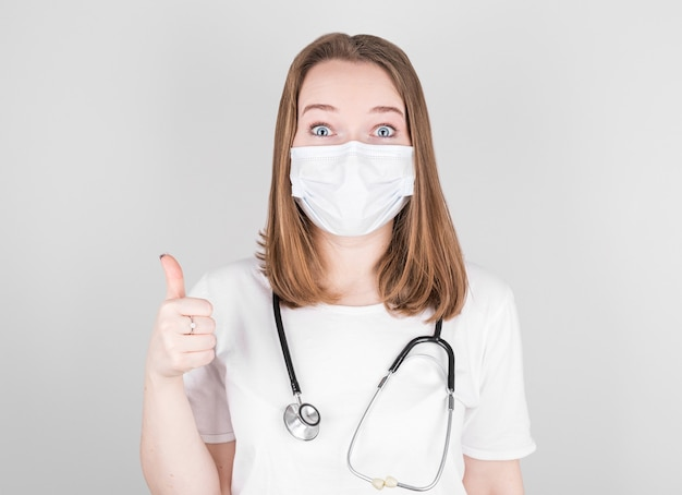 Ärztin in medizinischer kleidung mit einer schutzmaske im gesicht zeigt ihre daumen als zeichen des glücks