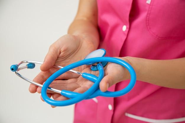 Ärztin in rosa medizinischer uniform hält stethoskop in ihren händen. lebens- und krankenversicherung. berufliche prüfungen. medizin und gesundheit. gesunder lebensstil. moderne medizin. medizinische versorgung.