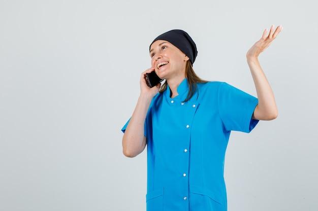 Ärztin in uniform, die auf smartphone mit handzeichen spricht und fröhlich schaut