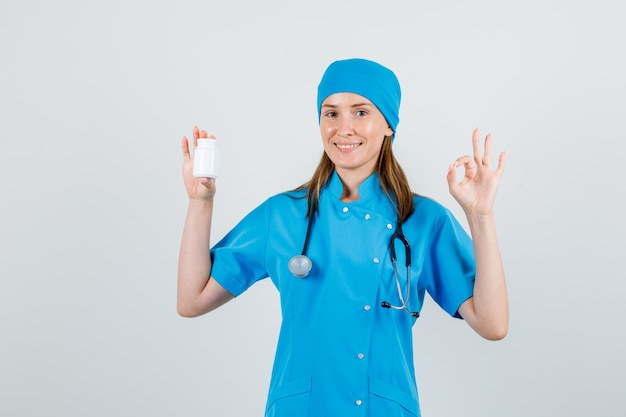 Ärztin in uniform, die flasche pillen mit ok-zeichen hält und fröhlich aussieht