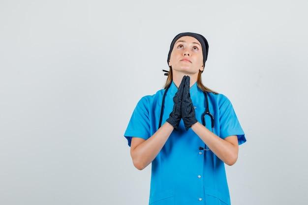 Ärztin in uniform, handschuhe halten hände in gebetsgeste und sehen hoffnungsvoll aus