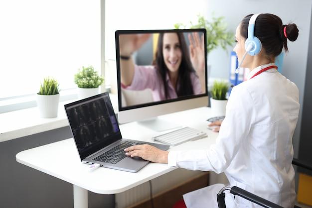 Ärztin in weißem kittel und kopfhörern führt online-konsultationen durch