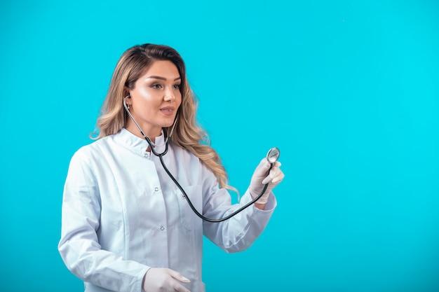 Ärztin in weißer uniform, die mit dem stethoskop prüft und aufmerksam zuhört.