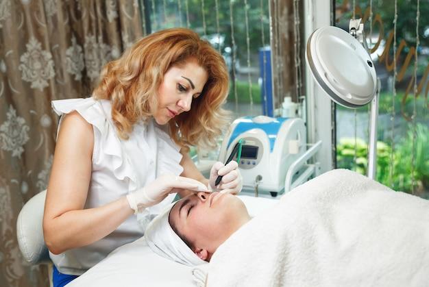 Ärztin kosmetikerin mit dermatoskop zur hautuntersuchung